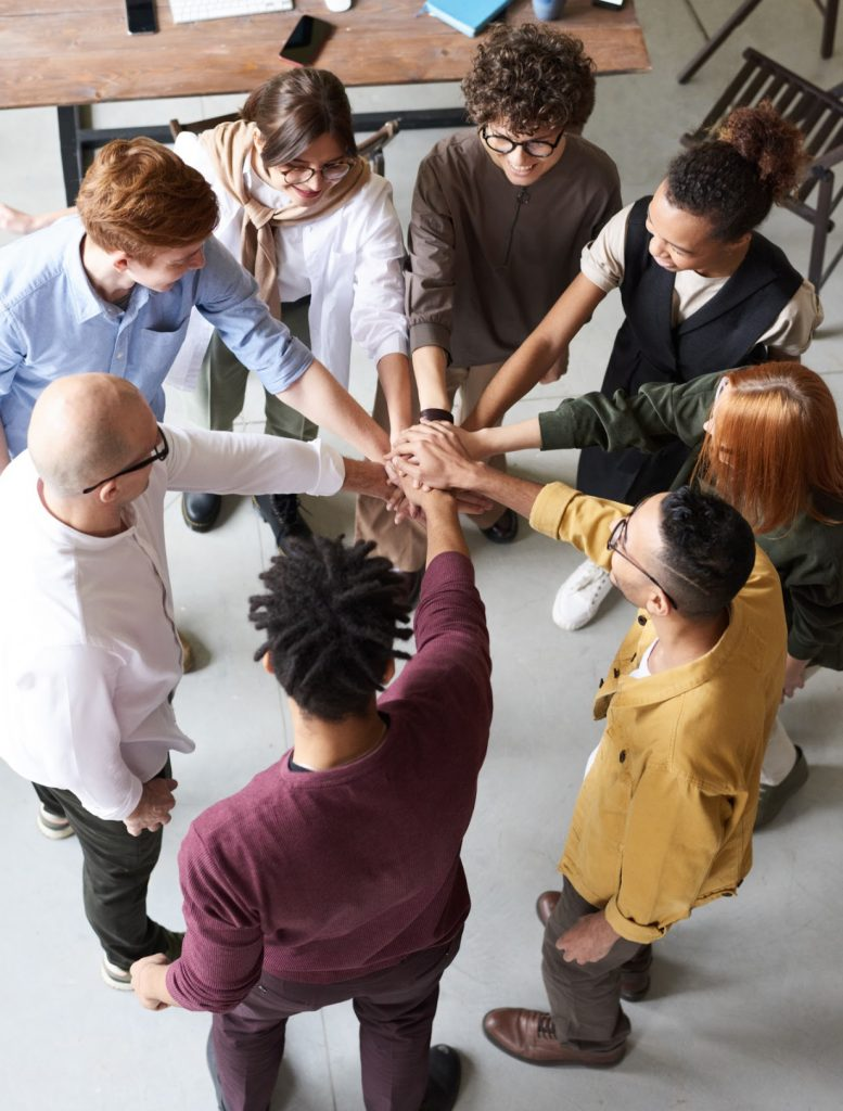 A diverse office with 8 people uniting hands for teamwork