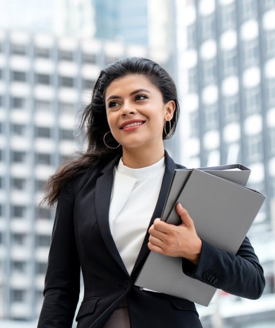 Young beautiful Latino businesswoman standing outdoors in city office building background